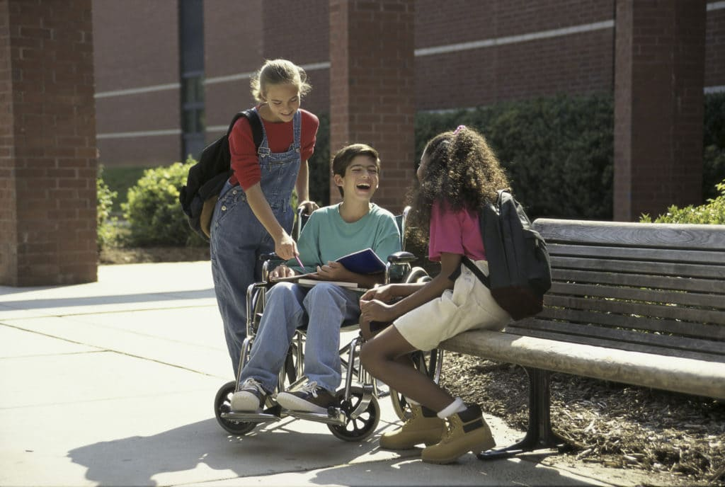 Three children gathered outside on a bench laughing and talking