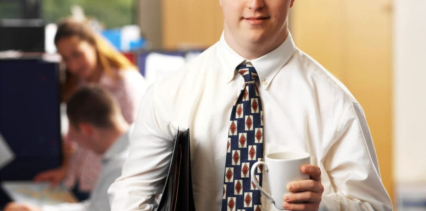 Image of young adult in business attire and a cup of coffee in hand