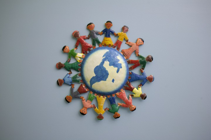 Wall art from the PEAL Center offices of several children holding hands in a circle around a globe.