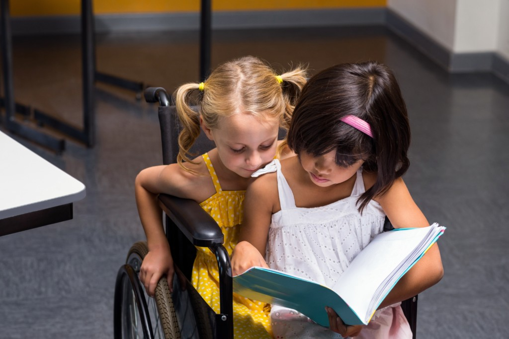 Girls sitting on wheelchair reading book