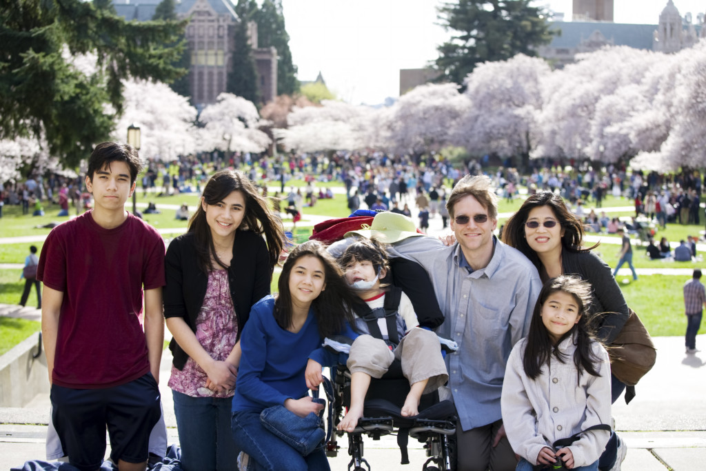 Multiracial family of seven in front of crowded field of cherry blossom trees. Youngest child is disabled with cerebral palsy.