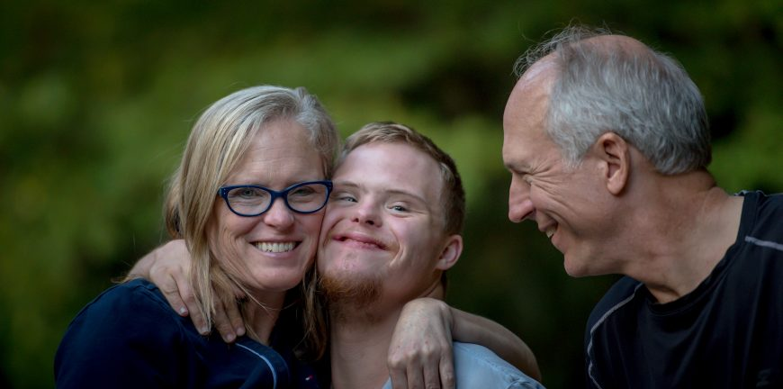 Mother, son, and father smiling and embracing